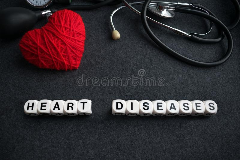 Word heart diseases from white cubes with letters on dark background with red thread heart and tonometer. Heart cardiovascular di. Seases inscription with royalty free stock images
