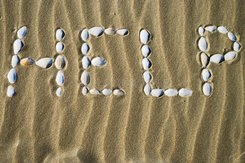 The word Help made of white seashells on sand. Calling for help in danger stock photos
