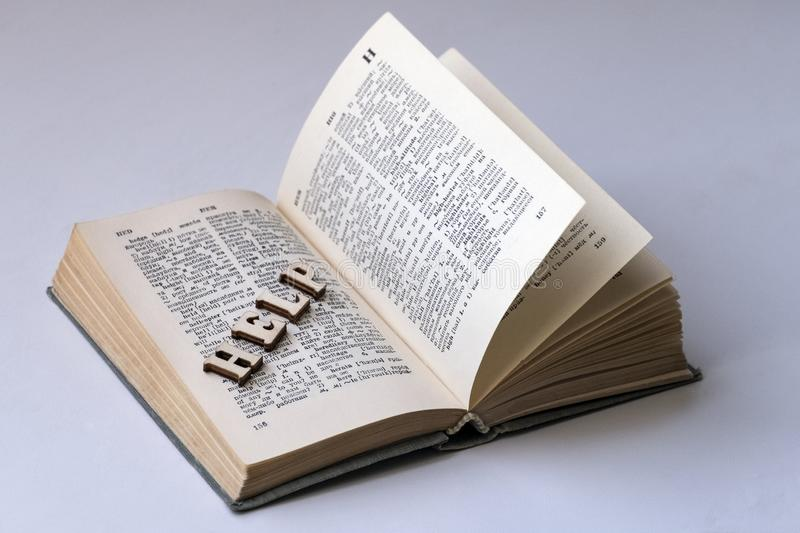 The word HELP from wooden letters is laid out on the page of the book. English-Russian dictionary. The concept of self-learning a. English-Russian dictionary royalty free stock images