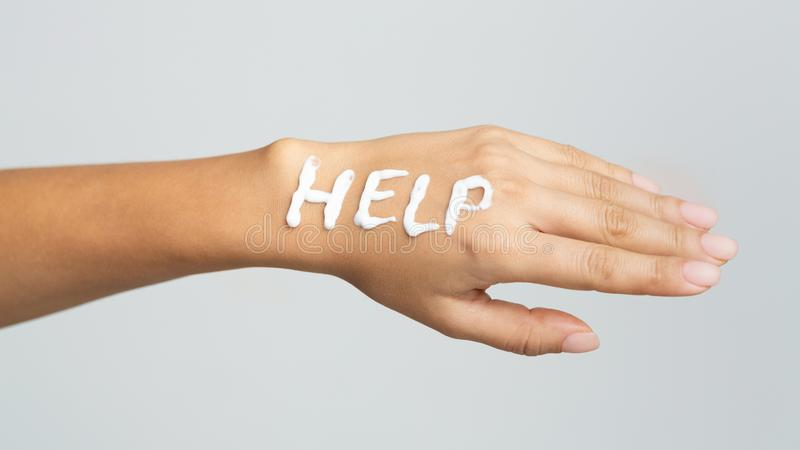 Word help written with cream on female hand royalty free stock photo