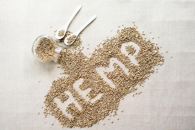 Word HEMP made of hemp seeds on linen background. Healthy eating supplement. Superfood concept. Top view. stock photos