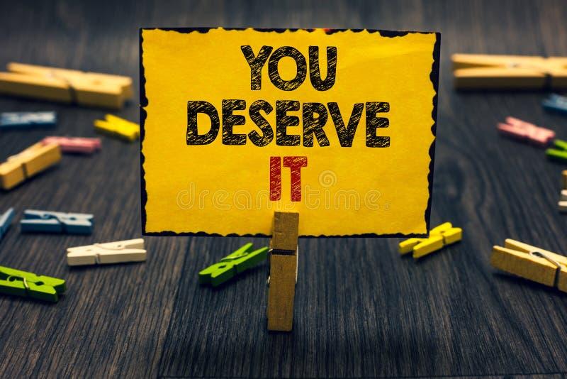 Word het schrijven de tekst u verdient het Het bedrijfsconcept voor Beloning voor goed uitgevoerd iets verdient het houten bureau stock foto's