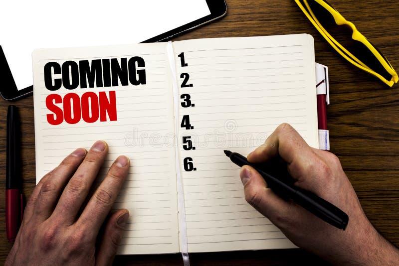 Word, het schrijven spoedig Komst Bedrijfsconcept voor in aanbouw Geschreven op boek, houten achtergrond met zakenmanhand, finge stock afbeelding