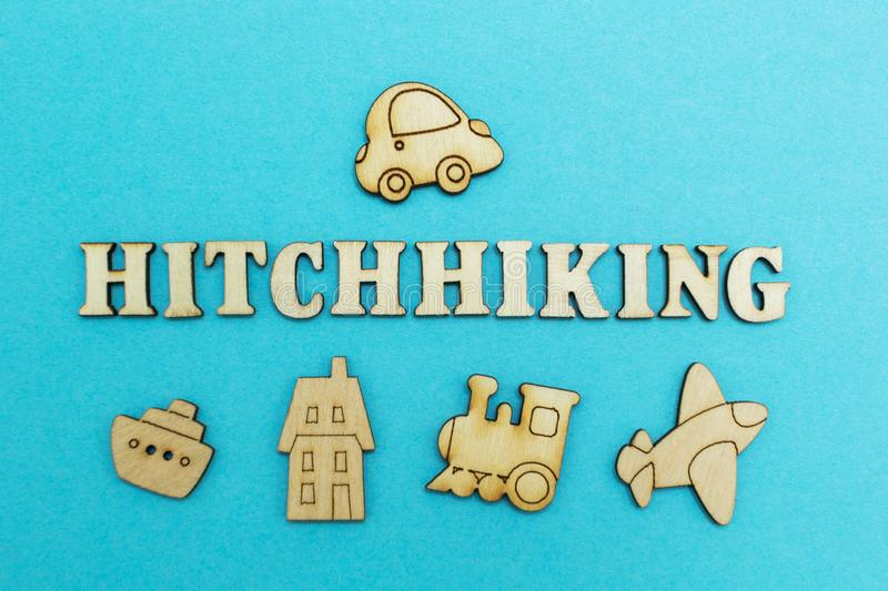 The word `hitchhiking` and the figure of the car on a blue background from above, plane, train, ship, hotel - from below.  stock image
