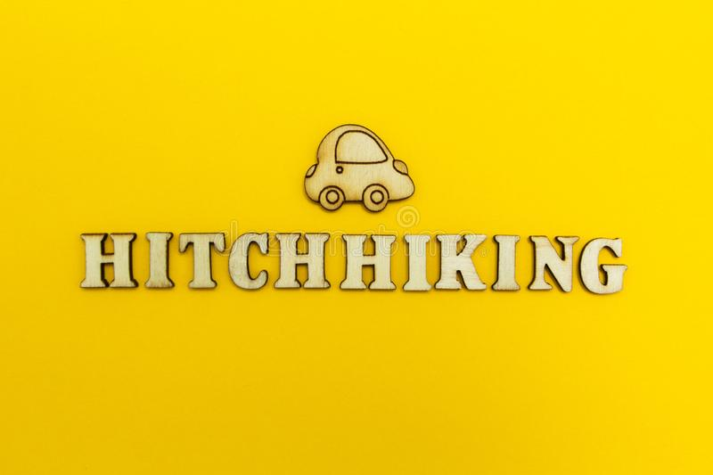 The word `hitchhiking` and the figure of the car on a yellow background.  royalty free stock photos