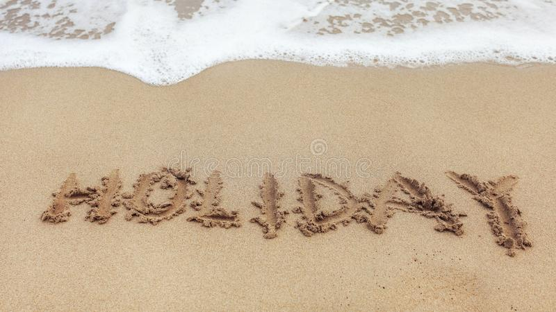 Word HOLIDAY written on wet sand of beach, small spot of white sea water in top part.  royalty free stock photo