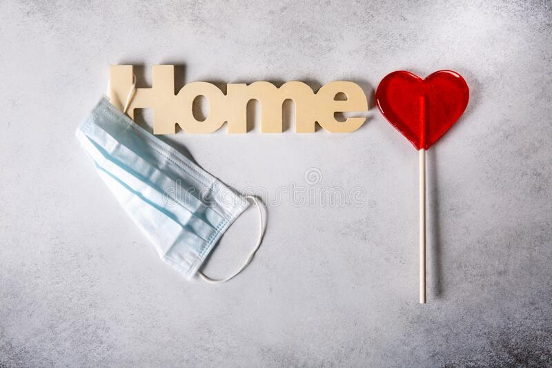 Word Home, protective medical mask and red heart. Stay home, social isolation,  coronavirus prevention concept. Top view, flat lay. Copy space stock photos