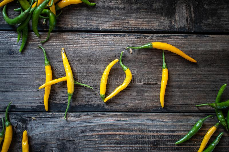 Word HOT made of raw organic yellow and green chili cayenne peppers royalty free stock image