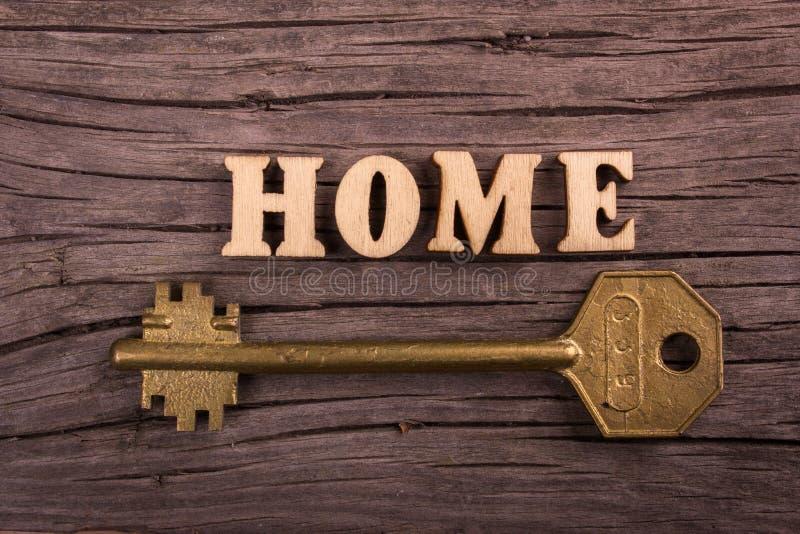 Word huis dat van houten brieven met een sleutel wordt gemaakt stock fotografie