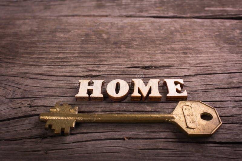 Word huis dat van houten brieven met een sleutel wordt gemaakt stock foto