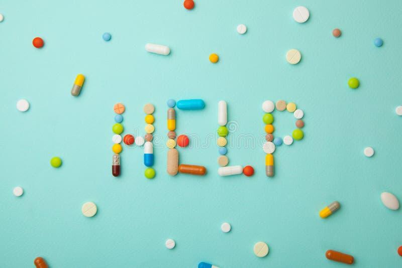 Word HULP van gekleurde pillen en capsules op groene achtergrond Welke geneesmiddelen om beter te kiezen, wat zal helpen stock fotografie
