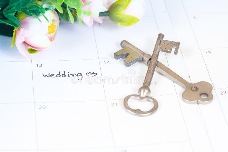 Word huwelijk op kalender met bloemen en oude sleutel stock fotografie