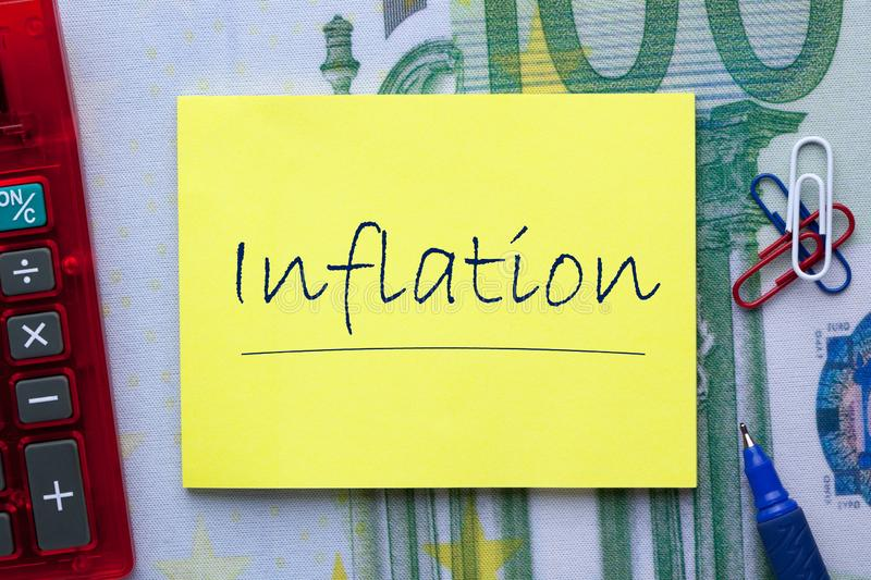 Word Inflation Concept. Word inflation written on note with pen a side and office supplies. Business concept royalty free stock image
