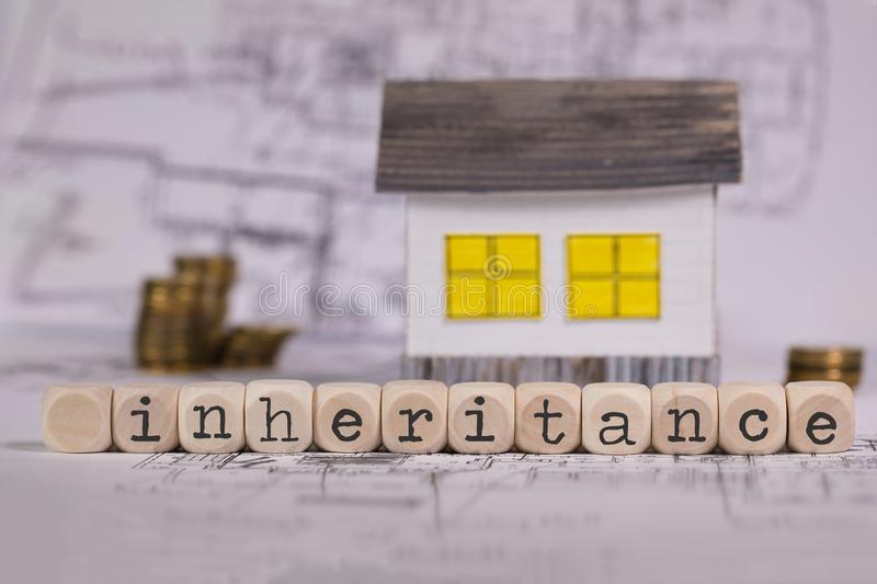 Word INHERITANCE composed of wooden letter. Small paper house in the background. Closeup stock photos