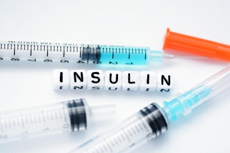 The word insulin spelled with plastic letter beads next to a syringe royalty free stock images