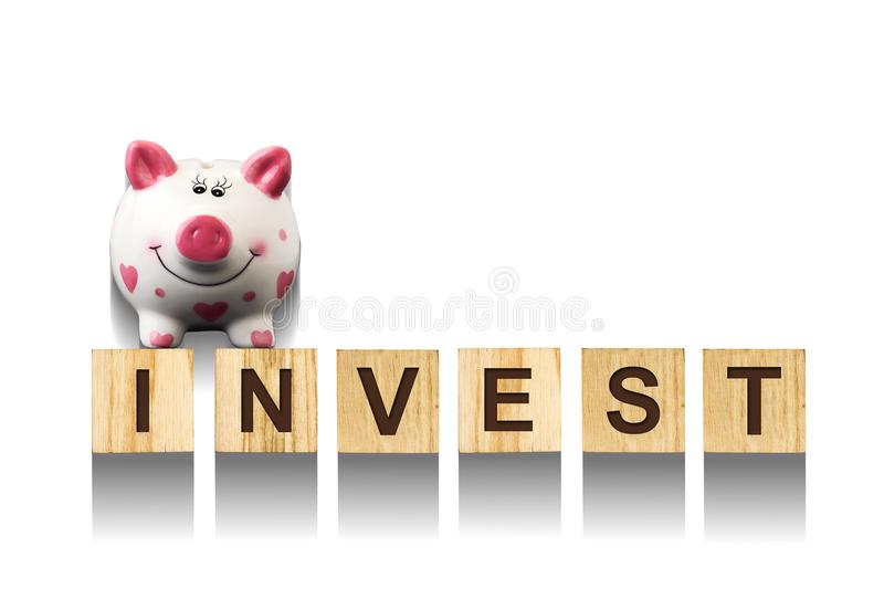 Word Invest, composed of letters on wooden construction cubes with piggy bank. White background, isolated Concept business, financ stock images