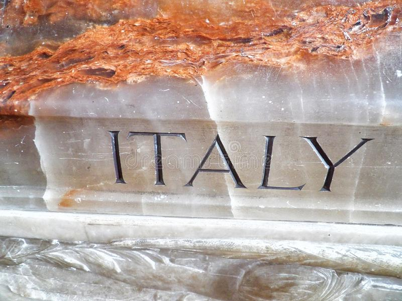 The word Italy carved into marble on a sarcophagus casket inside a church stock photos
