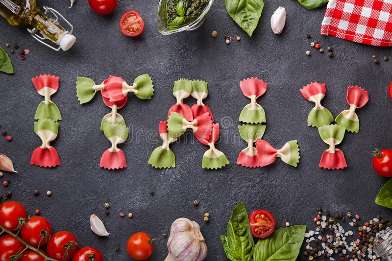 Word Italy from farfalle pasta with cherry tomatoes, garlic, basil, pesto, pepper mix, salt and napkin stock image