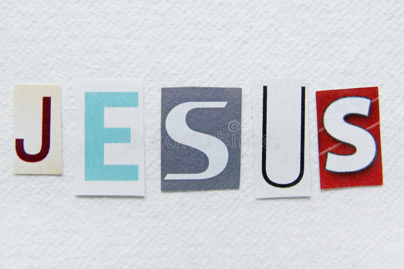 Word jesus cut from newspaper on handmade paper texture. Word jesus cut from newspaper on white handmade paper texture royalty free stock photos
