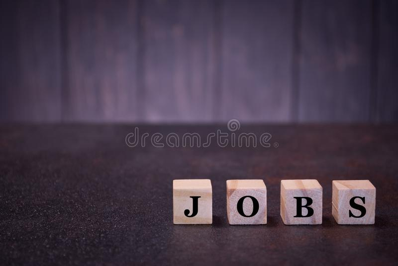 The word jobs on wooden cubes, on a dark background, light wooden cubes signs, symbols signs stock photography