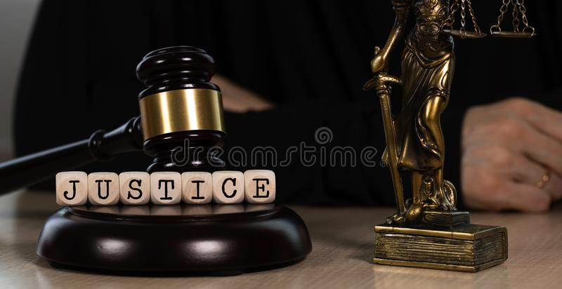 Word JUSTICE composed of wooden dices. Wooden gavel and statue of Themis in the background royalty free stock photography