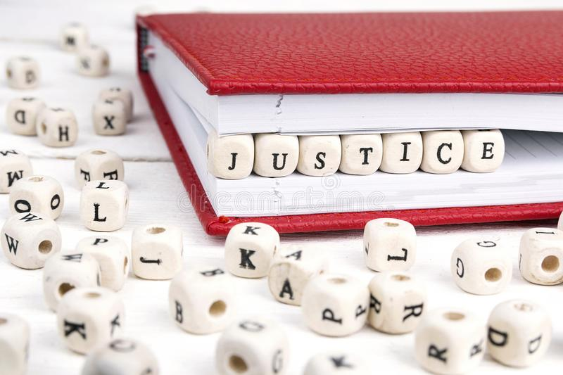 Word Justice written in wooden blocks in red notebook on white w stock photos