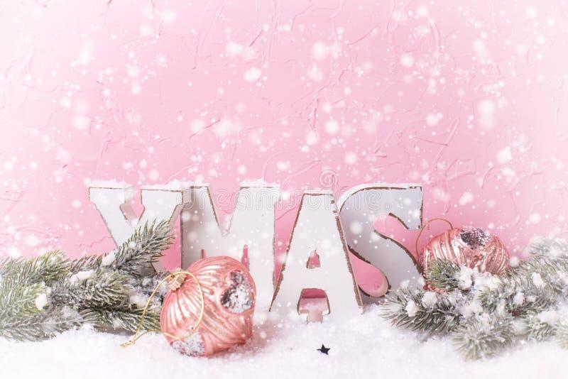 Word Kerstmis van houten brieven wordt gemaakt, vertakt zich bontbomen, decoratie tegen roze geweven muur die Getrokken sneeuw Pl royalty-vrije stock foto