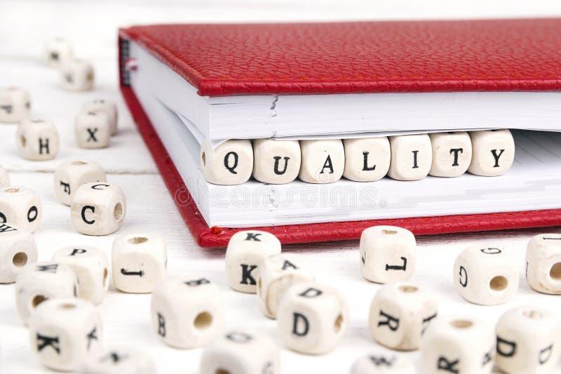 Word Kwaliteit in houten blokken in rood notitieboekje op wit w wordt geschreven dat royalty-vrije stock fotografie