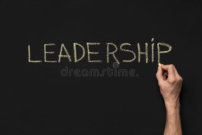 Word Leadership written with white chalk on blackboard. Man writing word Leadership with yellow chalk on blackboard, copy space royalty free stock image