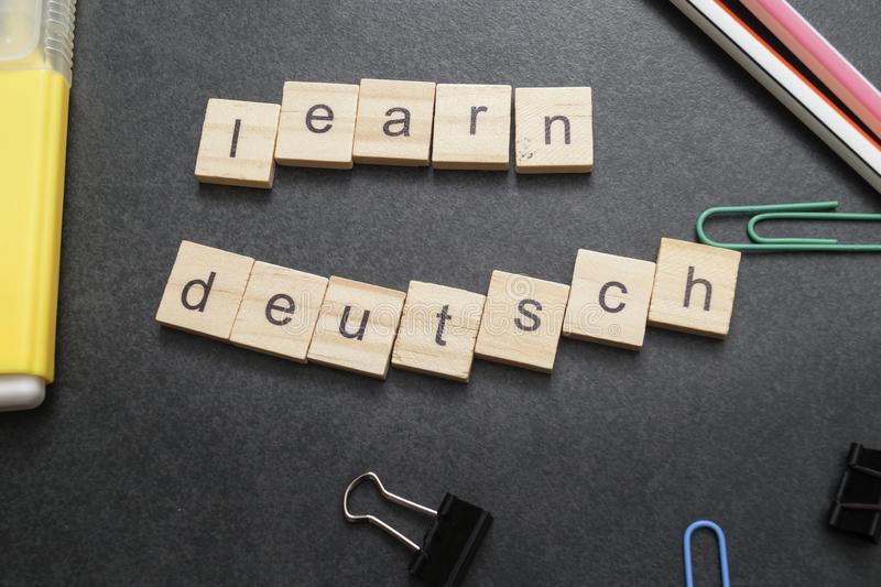 Word LEARN DEUTSCH written on wood block. Close up stock images