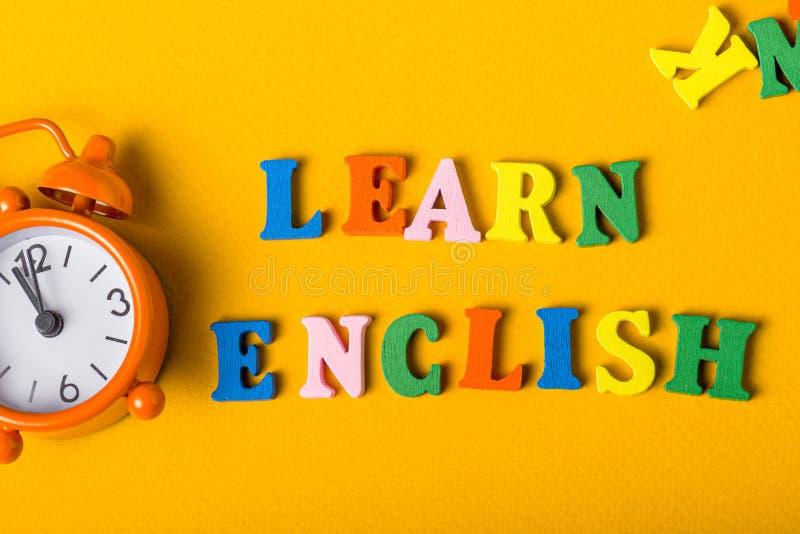 Word LEARN ENGLISH napisany drewnianymi literami na pomarańczowym biurku mały zegar Koncepcja kursów języka angielskiego zdjęcie stock