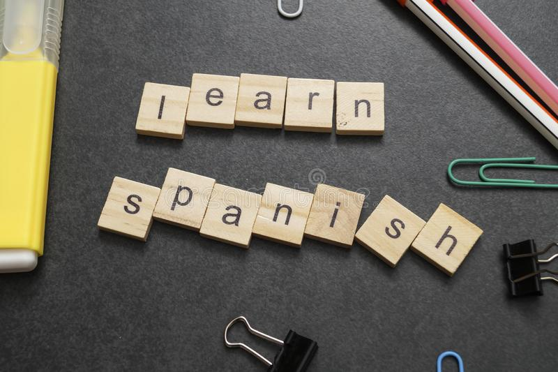 Word LEARN SPANISH written on wood block. Close up stock image