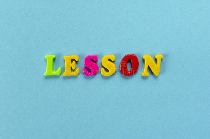 Word `lesson` of colored plastic magnetic letters on blue paper background stock image