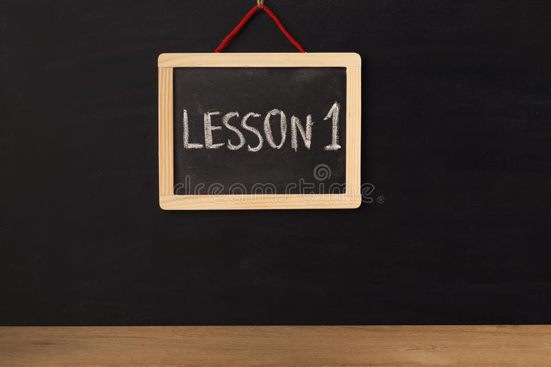 Word lesson 1 written on miniature chalkboard stock image