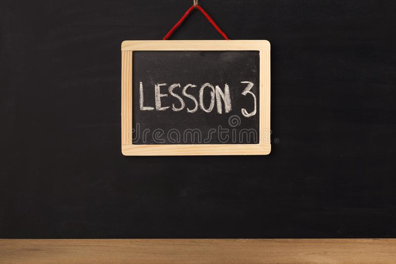 Word lesson 3 written on miniature chalkboard royalty free stock photo