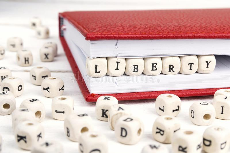 Word Liberty written in wooden blocks in notebook on white wooden table. royalty free stock images