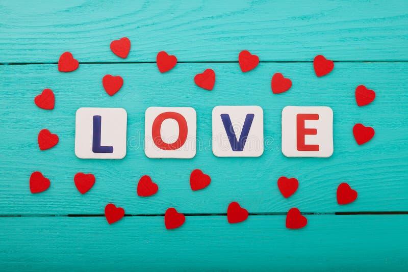 Word liefde en harten op blauwe houten achtergrond Hoogste mening De ruimte van het exemplaar Spot omhoog Valentine-moederdag stock foto