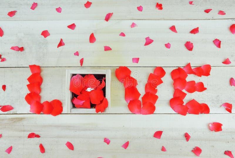 Word liefde met roze bloemblaadjes en doos met enige steen die rin wordt geschreven stock foto's