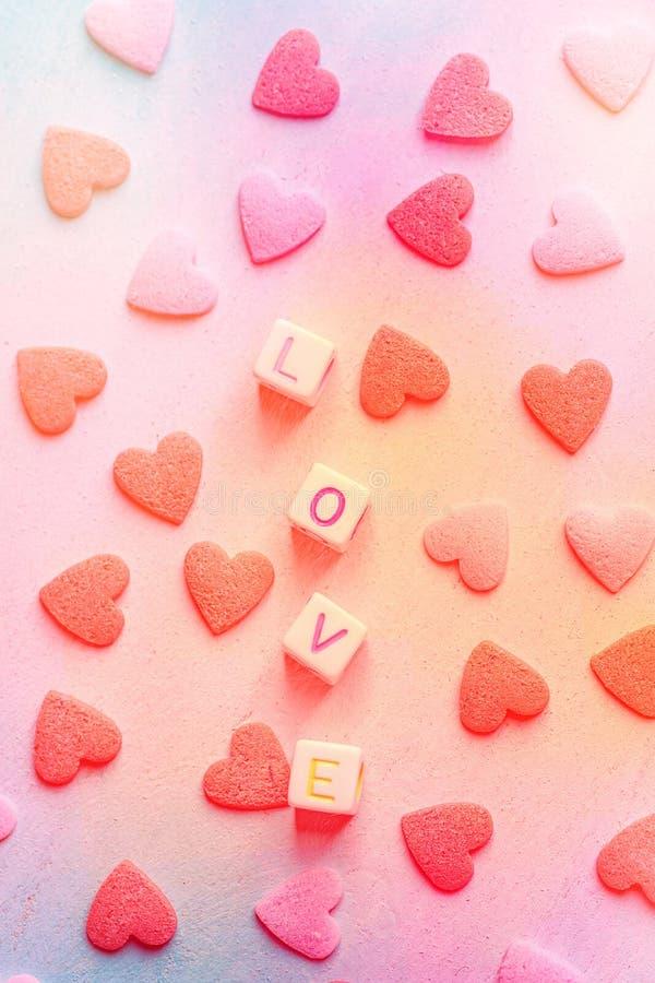 Word Liefde van Brievenkubussen die wordt geconstrueerd Rozerood Sugar Candy Sprinkles Multicolored achtergrond van de pastelkleu royalty-vrije stock fotografie