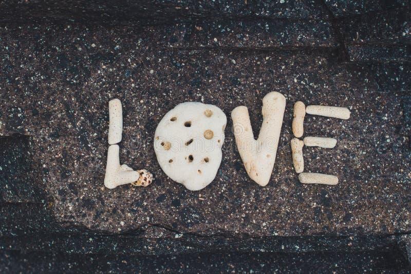 Word Liefde van shells wordt gemaakt op een granietsteen die wordt verzameld stock foto's