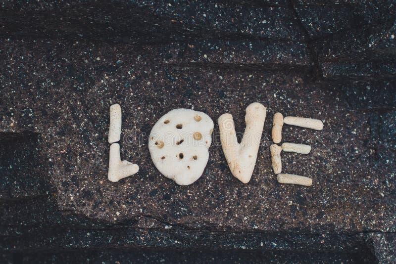 Word Liefde van shells wordt gemaakt op een granietsteen die wordt verzameld stock afbeeldingen