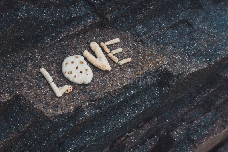 Word Liefde van shells wordt gemaakt op een granietsteen die wordt verzameld royalty-vrije stock afbeeldingen