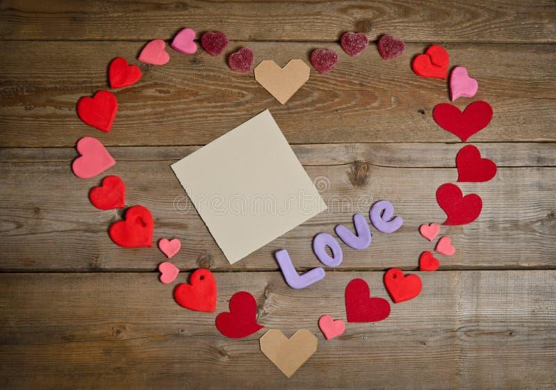 Word Liefdesamenstelling op de houten raadsoppervlakte en vele harten stock foto