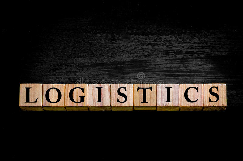 Word LOGISTICS isolated on black background. Word LOGISTICS. Wooden small cubes with letters isolated on black background with copy space available. Concept royalty free stock images