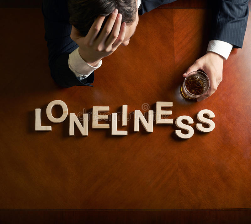 Word Loneliness and devastated man composition. Word Loneliness made of wooden block letters and devastated middle aged caucasian man in a black suit sitting at stock photos