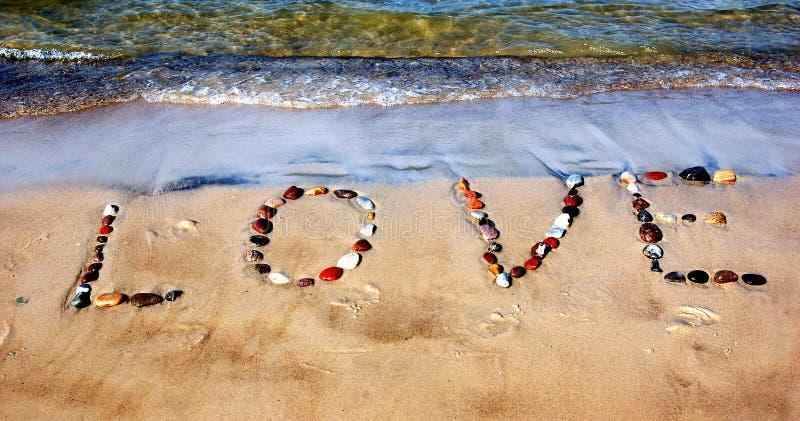 Word LOVE on beach sand stock photo