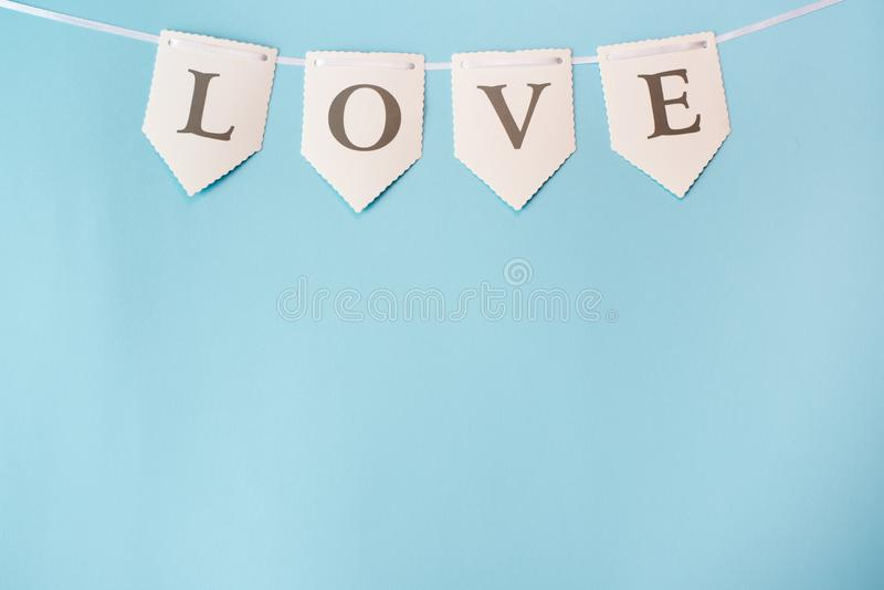 Word love on blue background with copy space. St. Valentine Day, love or wedding day concept. pastel color stock photography