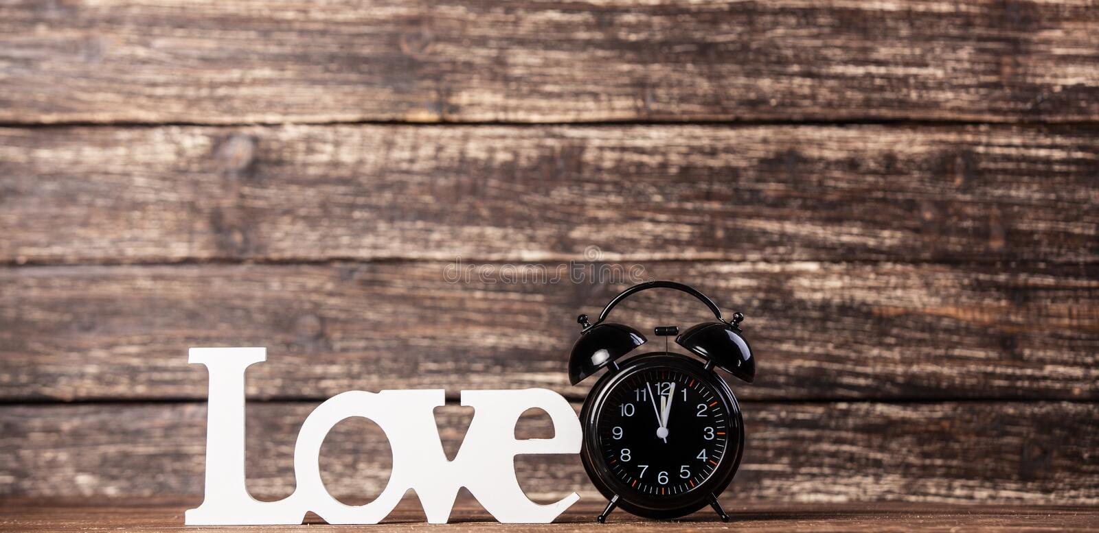 Word Love and clock. Word Love and alarm clock on wooden table stock photography