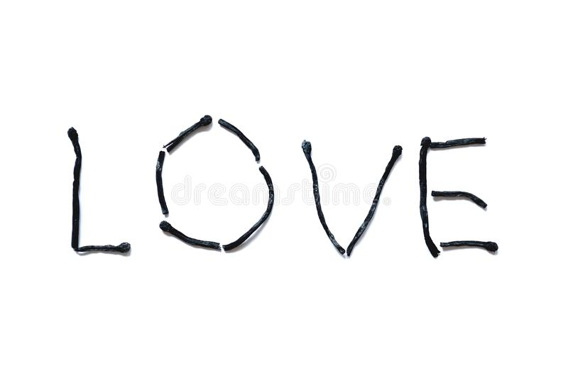 The word love close-up, lined from burnt down matches, isolated on a white background. stock image