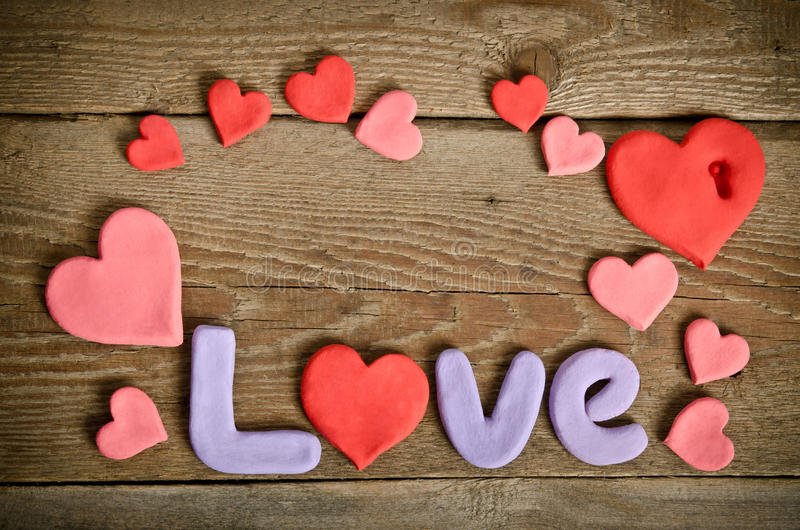 Word Love composition on the wooden board with hearts. Word Love composition on the wooden board surface and many hearts handmade around. Letters and hearts made royalty free stock photo